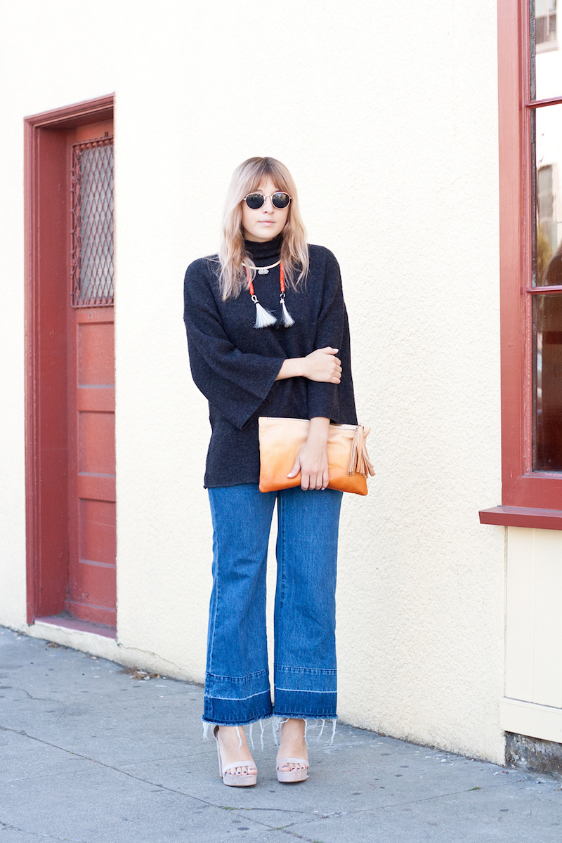 Mature Boho Outfit and Boho Chic San Francisco Style worn by Bryn Newman of Stone Fox Style a SF Fashion Blog Bryn shows how to wear cropped frayed denim and flare sleeved sweaters for the fall with a hand dyed clutch by ayk and a horse hair tassel necklace she made herself