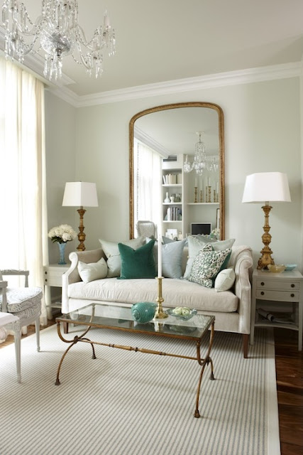 sarah richardson's living room with pale green sea green accents with gold coffee table, brass lamps arched curved gold mirror