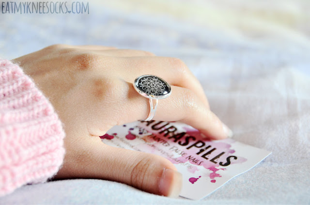 The ring from LaurasPills is silver and adjustable, with the print enhanced by a glass cabochon, just like the necklace. The metal portion of the ring is lightweight but not flimsy, and it fits comfortably.