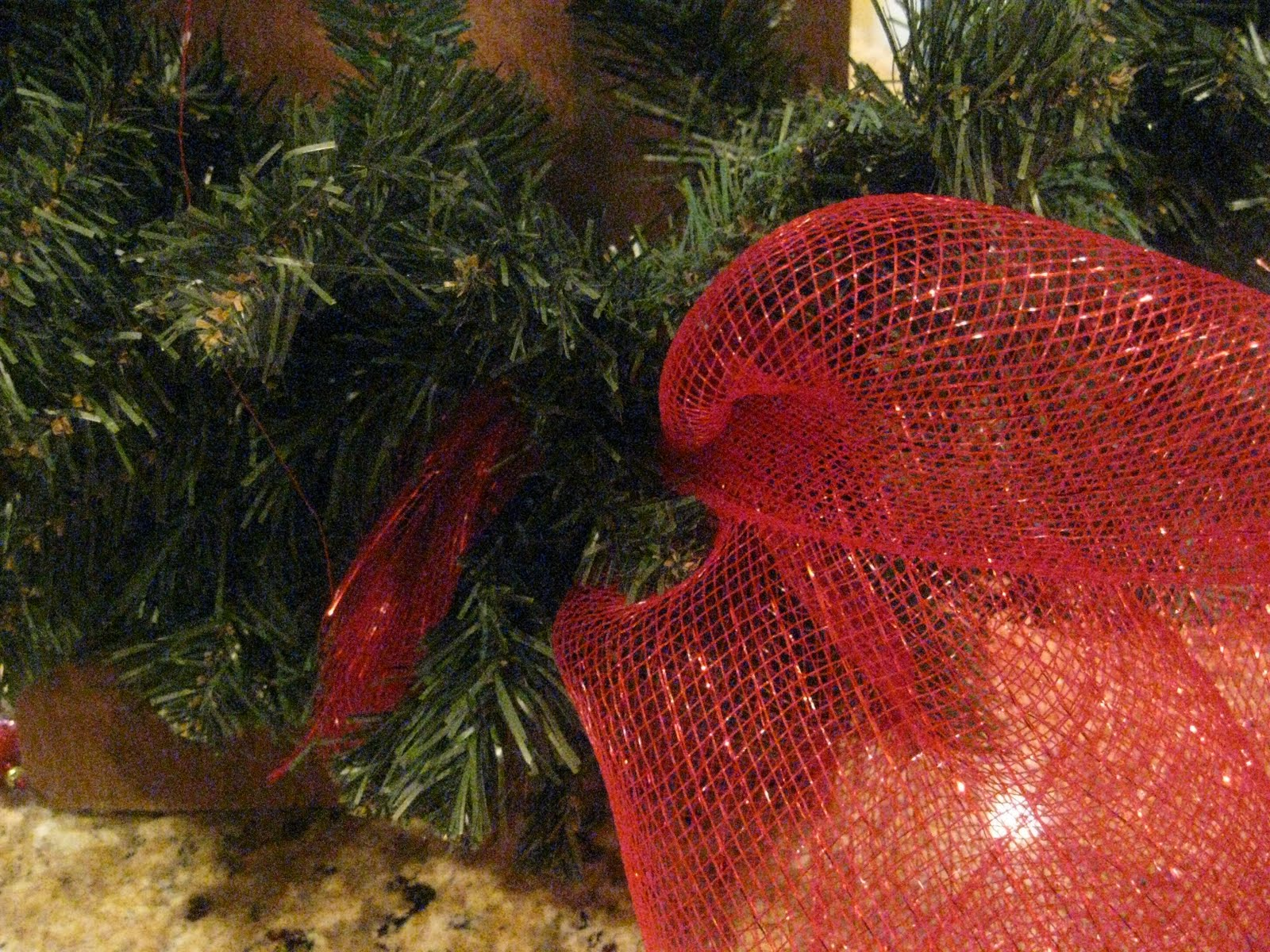 start adding the mesh all around the wreath wrapping the greenery around it about every 6 to 7 inches - Decorating A Christmas Wreath With Mesh Ribbon