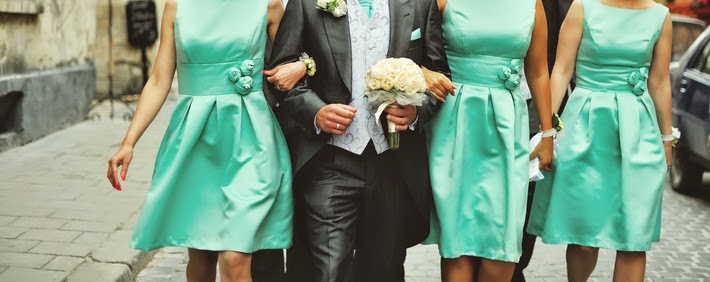 bridesmaids in aqua dresses walking with groom
