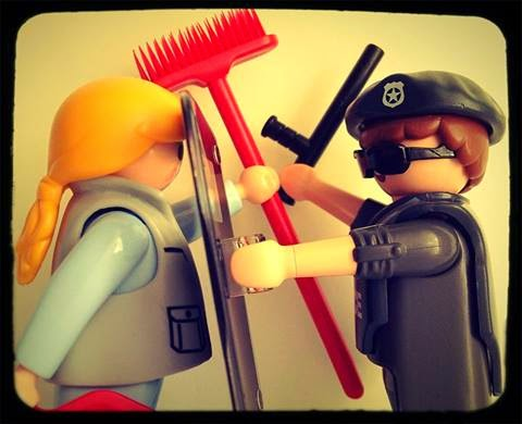 A toy figure of a cleaner battles with a toy figure of a police officer.