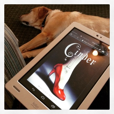 An enormous yellow lab, Buster, flops on his side with his legs outstretched. Perched above him is a white Kobo with Cinder's cover on its screen. The cover features a pale foot in a shiny, red, high-heeled shoe. Mechanical workings are visible through the person's skin.