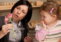 NAMC montessori views on infant toddler behavior child and montessori parent with flower