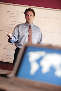Photo of professor teaching, with computer featuring a world map in the foreground.