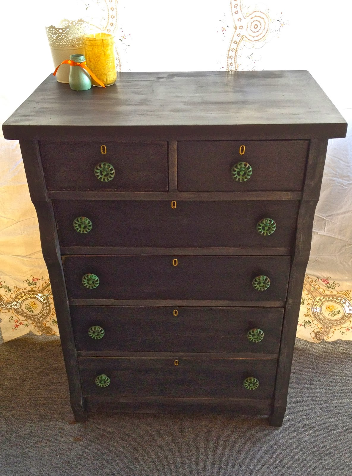 black antique dresser with green knobs