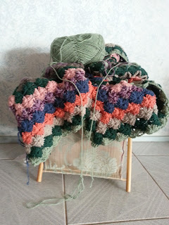 partly finished blanket with ball of yarn in knitting bag