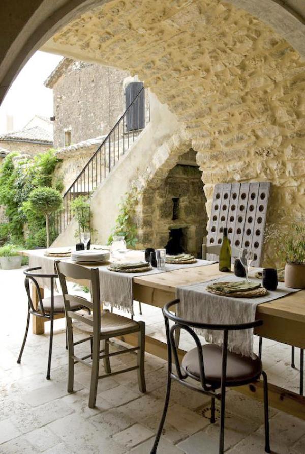 mesa de comedor bajo un arco de piedra