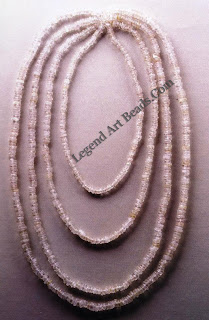 These disk-shaped rock crystal beads are styled in four single chains. The necklace clasps at the base of the neck and shows an almost regular scaling on the décolleté.