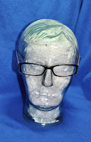 photo of purple/blue reader glasses on a clear glass head filled with white yarn