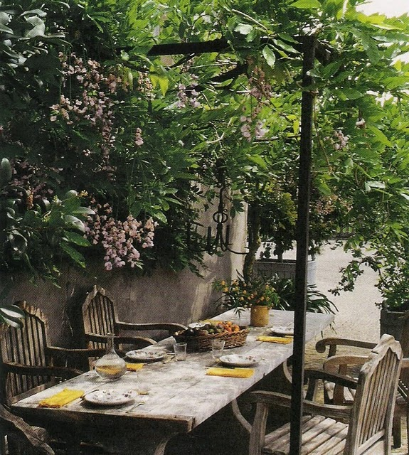 Outdoor dining with wood table and chairs lush greenery canopy, image from Axel Vervoordt's Timeless Interiors, edited by lb for linenandlavender.net (l&l)