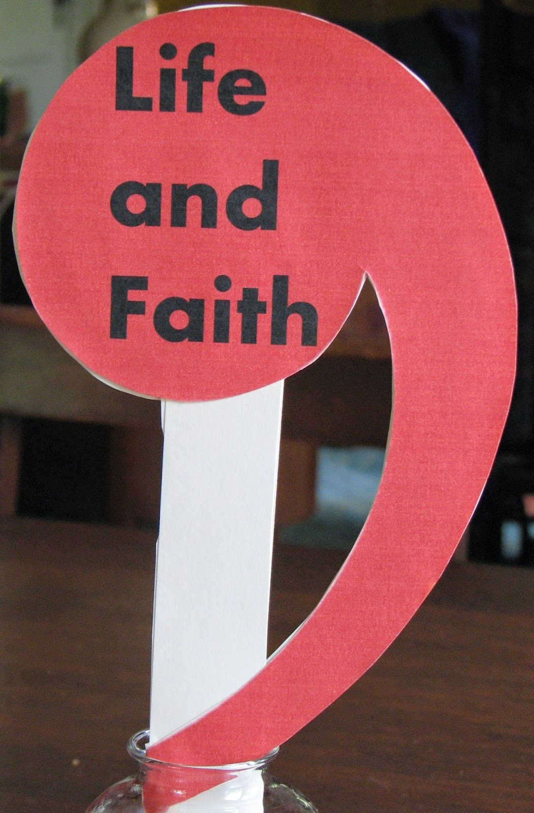 sign of red comma printed with the words Life and Faith