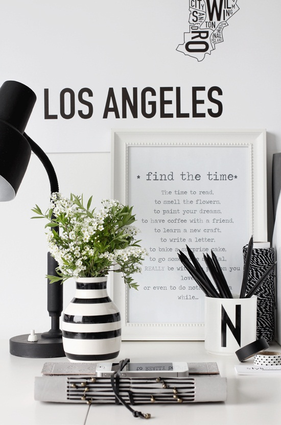 home office with a black desk lamp, black and white striped vase holding flowers, a white monogrammed N mug holding black pen, with a quote about finding the time in a white frame