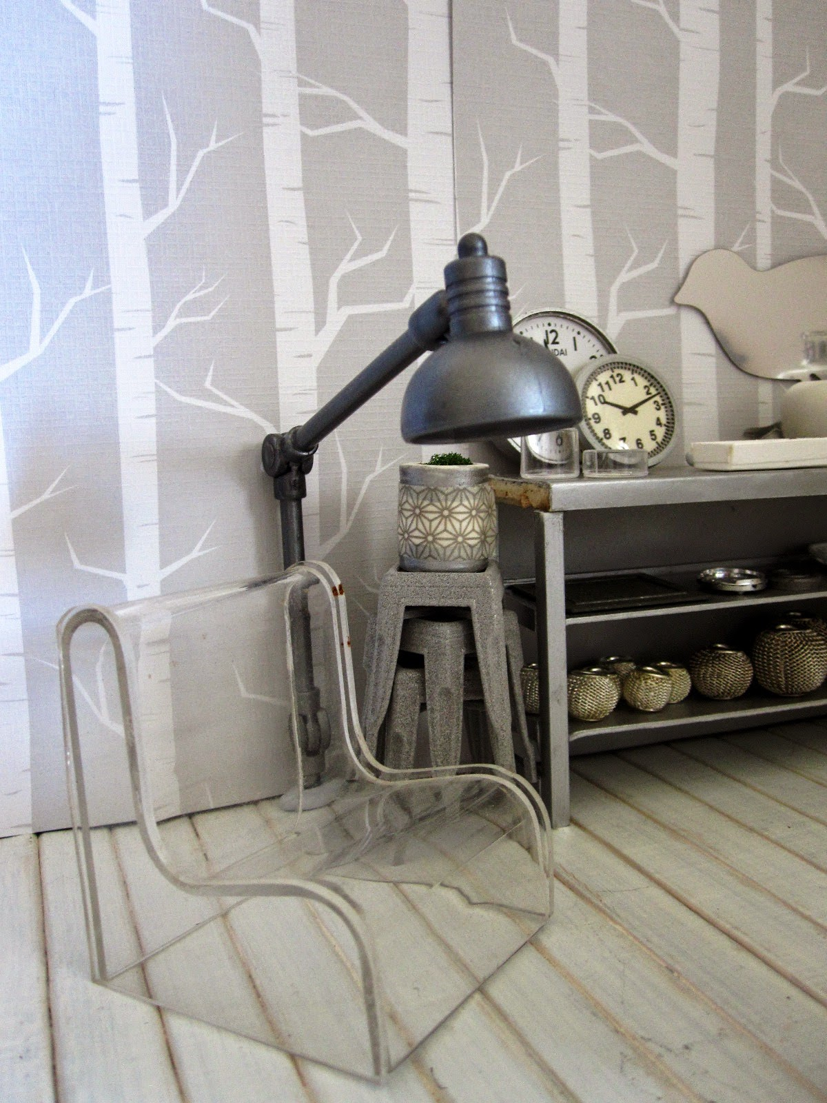 Corner of a modern dolls' house miniature homeware shop in grey and white. On display is a clear perspex chair, a giant floor lamp, a stack of cafe stools and a grey metal shelving unit with various grey-coloured decor pieces displayed.