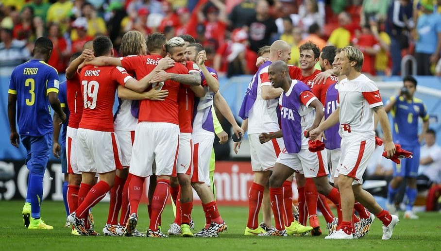 Swiss players celebrate after the group E World Cup soccer match between Switzerland and Ecuador at the Estadio Nacional in Brasilia, Brazil, Sunday, June 15, 2014. Switzerland won the match 2-1.