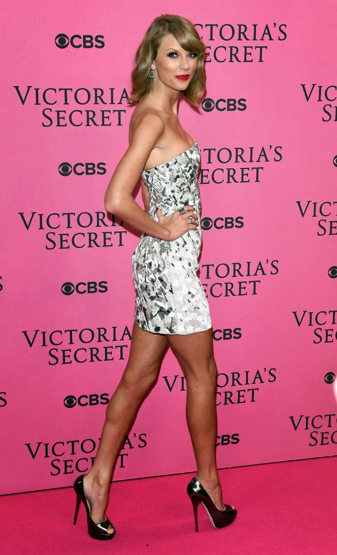 Taylor Swift arrives for the 2014 Victoria's Secret Fashion Show in a strapless silver mini dress