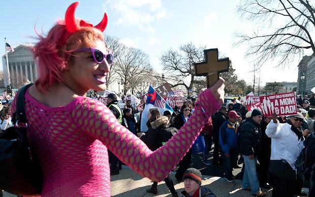 Uma Drag Queen mostra uma cruz para manifestantes contrários ao casamento entre pessoas do mesmo sexo nos EUA (Foto: Nicholas Kamm/AFP)