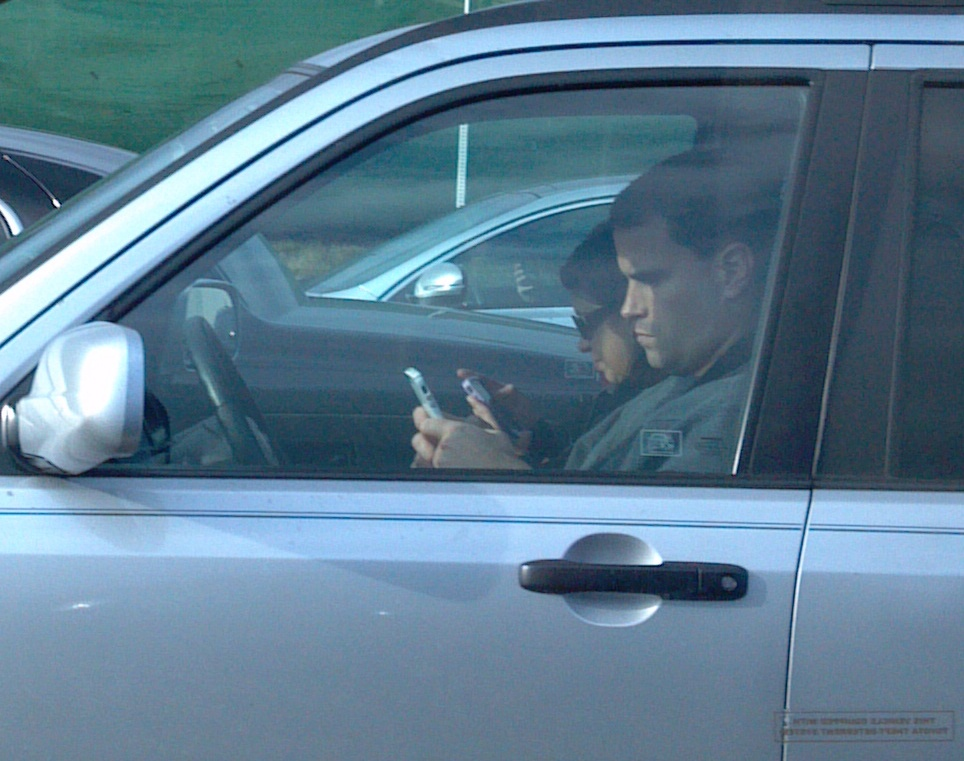 person texting or looking at their phone while behind wheel of their car