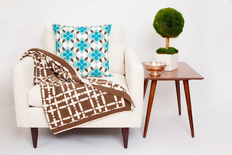 Nbaynadamas Cotton Collection pillow in Coco's Flower and Nbaynadamas throw in Plaid on a white armchair next to a wood side table with a small topiary