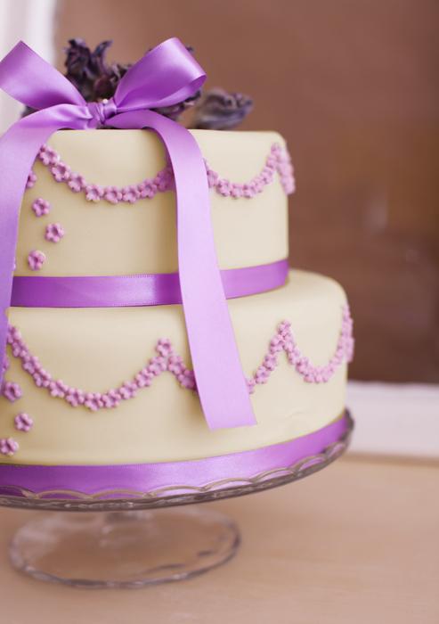 Kleine Hochzeitstorte mit hellgelbem Fondant, lila Zuckerblüten, lila ...