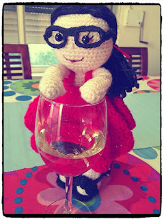 Kwokkie Doll is standing on a table next to a glass of white wine.