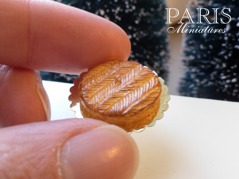 Galette des rois in miniature with thumb to show scale