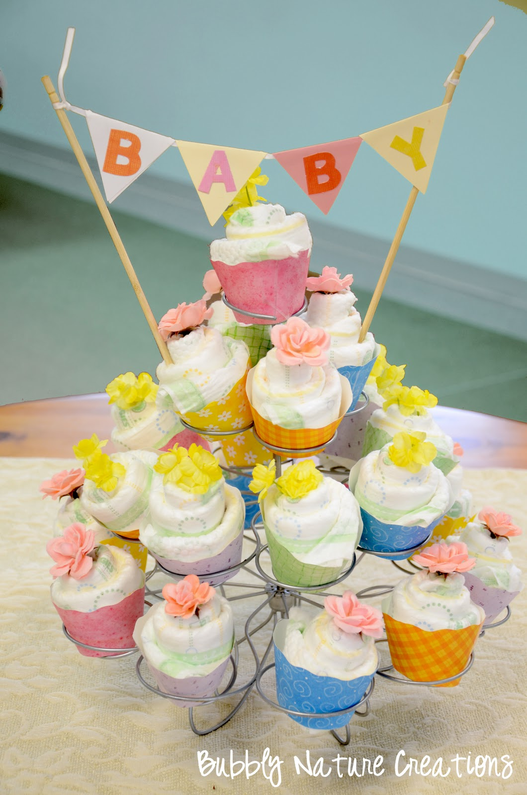 Diaper cupcakes tutorial sprinkle some fun for Baby shower diaper decoration