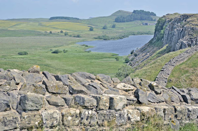 A section of the Wall in the foreground, with crags and a lake beyond