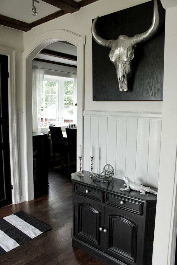 förebild på renovering i hallen, svart byrå, trägolv, buffelhuvud på väggen