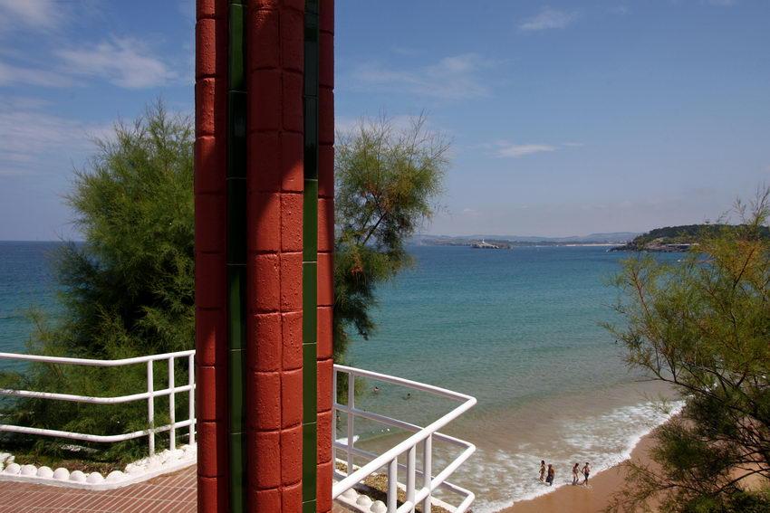Foto a partir de um miradouro com um pilar em primeiro plano. Em Baixo pessoas na praia e ao fundo a costa