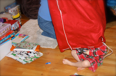 little girl sticking out of large Santa bag