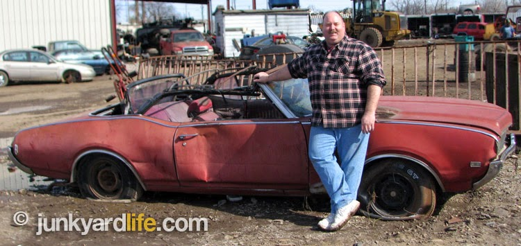 Keith Lively proudly stands by his latest hot rod project, a red 1969 Cutlass convertible,