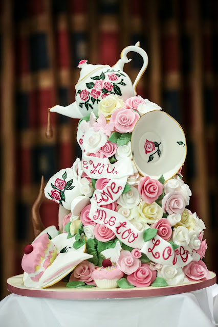 3d afternoon tea themed wedding cake with teacup on top pouring out liquid flowers cakes cups and saucers pink and green themed