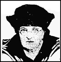 A bespectacled woman, past middle-age, staring intently into the camera. She wears a dark sailor-style hat and collar.