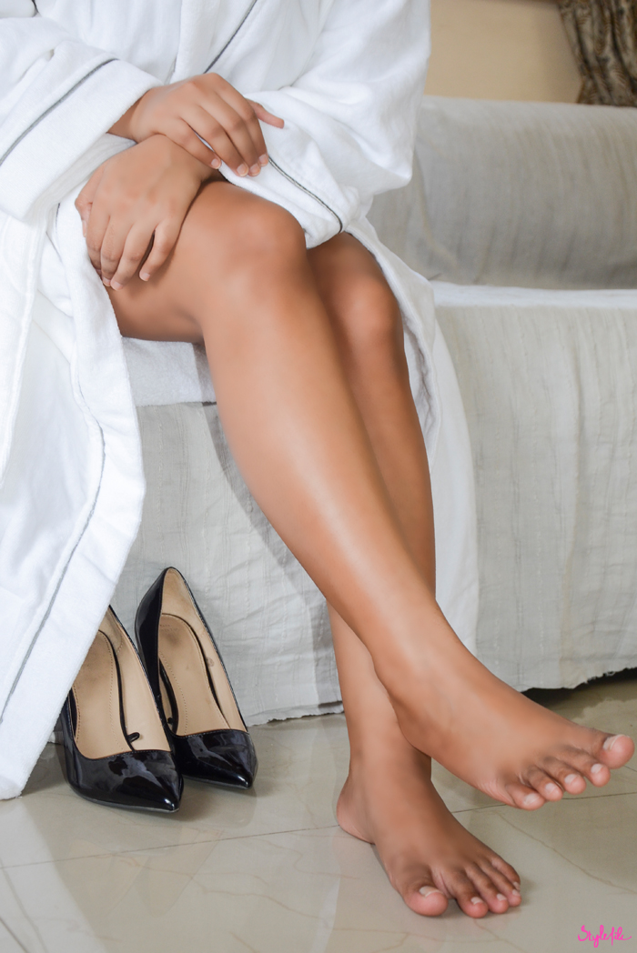 Dayle Pereira of Style File India displays her smoothly shaven legs while wearing a fluffy white bathrobe with black leather pumps
