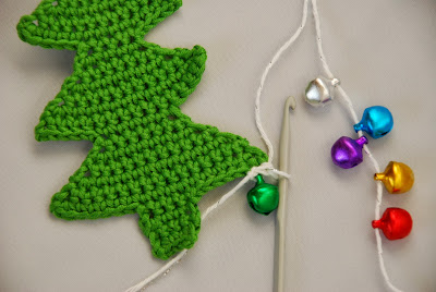 Crochet Christmas tree pattern and tutorial: image of crocheted snowy like border and first bauble worked onto tree