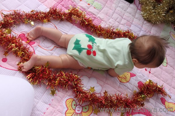 Holly on the bottom of baby Bee's onesie with tinsel
