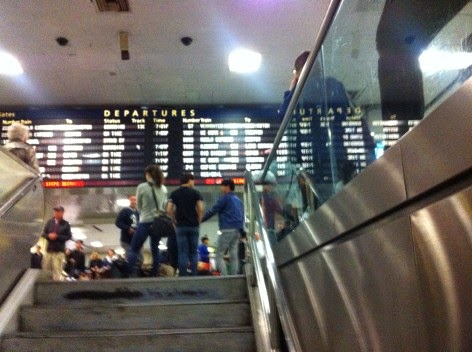 Make Amtrak Travel Less Stressfull - Follow this Tip at NY Penn Station - Image of staircase underneath the Departures/Arrivals sign Leading Down to Platforms