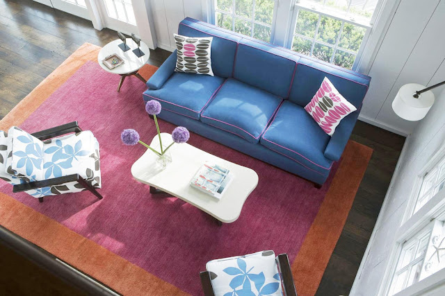 living room with stained wood floor, orange and purple area rug, blue sofa, white coffee table and accent table and two armchairs with white cushions with large blue and brown leaves printed on them