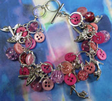 Cute charm bracelet has clusters of bright beads and buttons in pink with silver pewter fashion charms