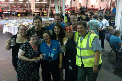 Group shot of nine people at Olympia raising a glass (or tankard) to my leaving.