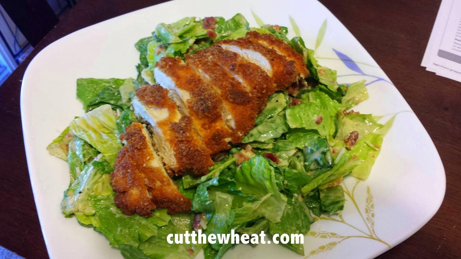 Boneless, skinless fried chicken breast over caesar salad