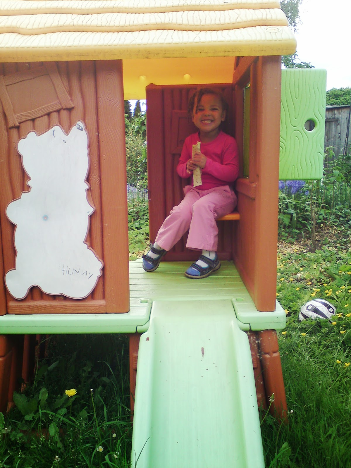 madam eating a wrap whilst sitting in a plastic playhouse in the garden