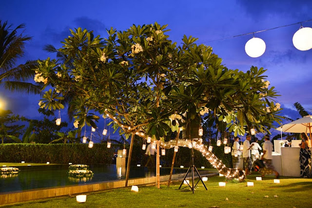 fairy lights wrapped around frangipani tree with hanging candles