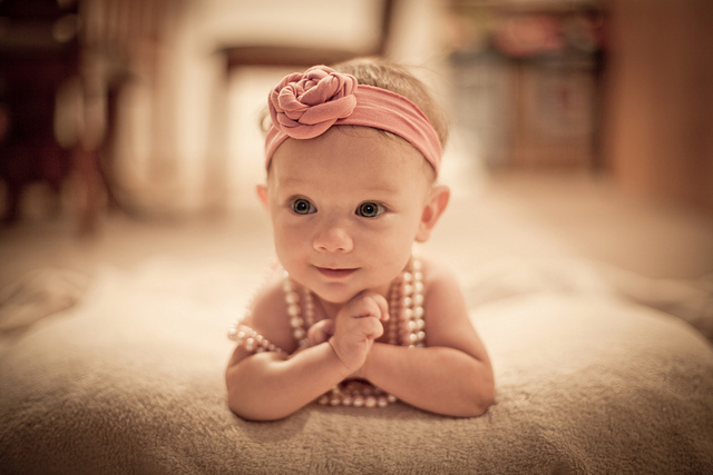 A smiling baby girl wearing a pink ribbon and pearls