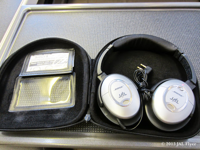 JAL First Class: Customized Bose QuitComfort 2 headphones with JAL logos on them.