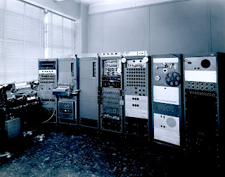 Original Mark I synthesizer as it appeared in 1955.  Pictured at the extreme left is the recording unit that generated the output in the form of a phonograph record.  The second cabinet from left contains the paper record drive for input.  The five cabinets to the right contain the synthesizer proper.
