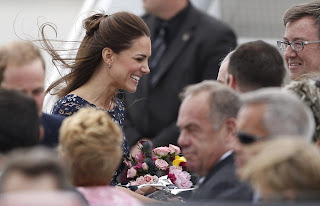At ease Kate smiles as she receives flowers from the Royal fans who lined up to meet the newlyweds at Ottawa's Macdonald-Cartier International Airport today.