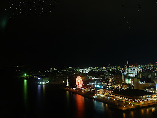 Lights and Ferris wheel of Harbour land reflected into the bay as seen from the Kobe Port Tower at night