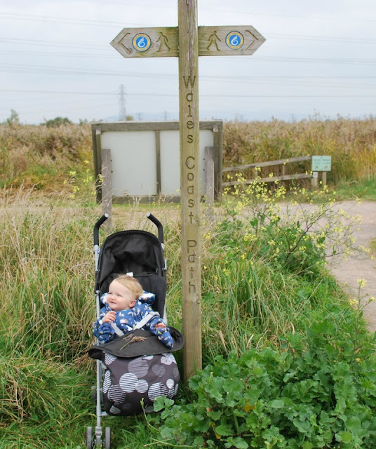 Baby in buggy next to Wales Coastal Path waymarker sign